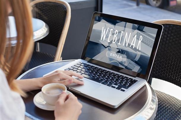 Kvinne følger webinar på PC, har kaffekopp ved siden av seg