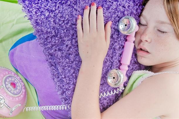 Jente sover med telefon