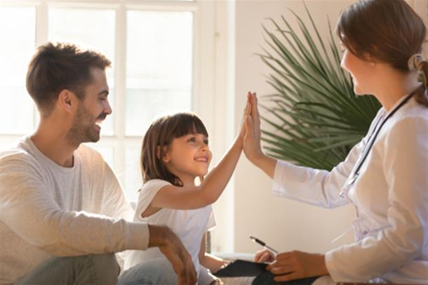 barn gjør high five med lege