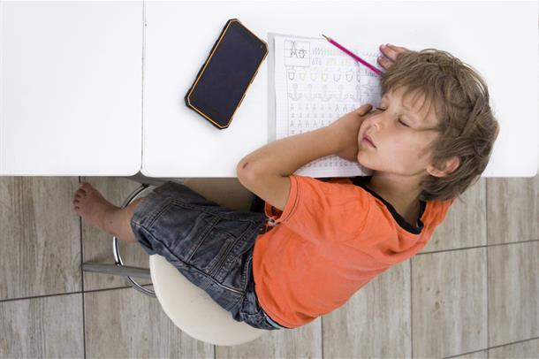Gutt sover på pulten
