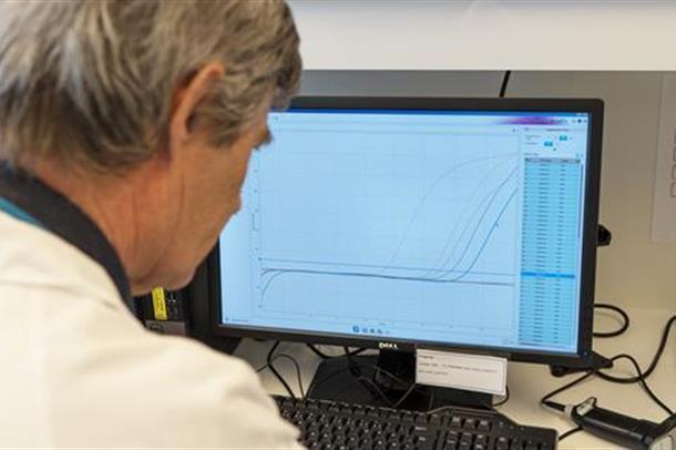 Foto av Fredrik Müller som sjekker antall positive korona-prøver