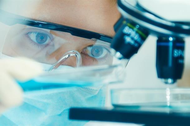 Illustrasjonsfoto av forsker som ser i mikroskop.