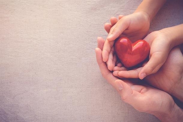 Illustrasjonsfoto av hender som holder et rødt hjerte.